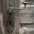 Old door handle on wooden door - Stock Photo