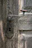 Old door handle on wooden door — Stock Photo
