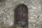 Castle wood gate on stone wall — Stock Photo