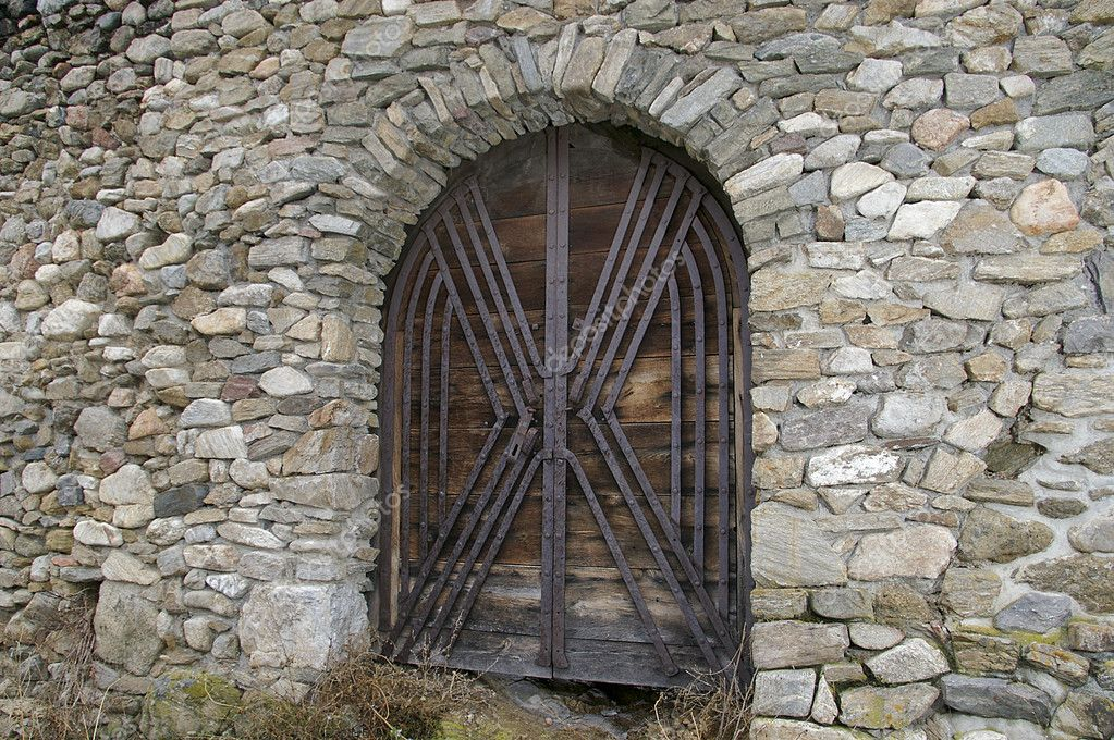 Castle wood gate reinforced metal on stone wall — Stock Photo #2193954