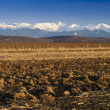 Mountain range snow peaks plowed field - Stock Photo