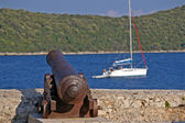 Old cannon at seaside with blue water — Stock Photo