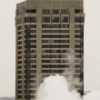 Tall apartment buiding in white smoke — Stock Photo