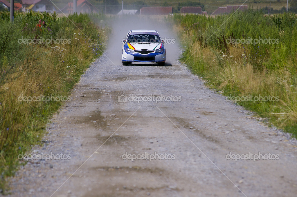 Rally car on gravel road front view with village houses in background — Stock Photo #2549186
