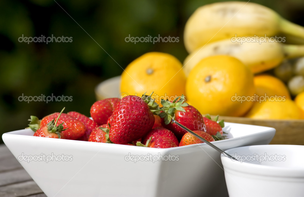 Bowl of strawberries in a garden outside — Stock Photo #1966851