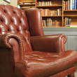 Old style armchair in front of bookshelv — Stock Photo