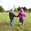 Stock Photo: Two children holding hands walking in co