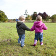 Two children holding hands walking in co — Stock Photo