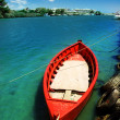Red fishing boat on blue water — Stock Photo