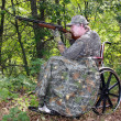 Wheelchair hunter with shotgun — Stockfoto