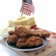 Fried chicken on checkerboard — Stock Photo