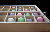 Pastel balls in a type case — Stock Photo