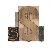 Four wood and metal dollar signs — Stock Photo