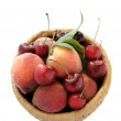 Peaches and cherries in a basket - Stock Photo