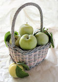 Fresh green plums in a pastel basket — Stock Photo