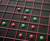 Red and green discs in a red grid — Stock Photo