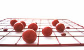 Red discs and balls on a red grid — Stock Photo