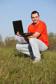 Boy in red t-shirt with laptop — Stock Photo