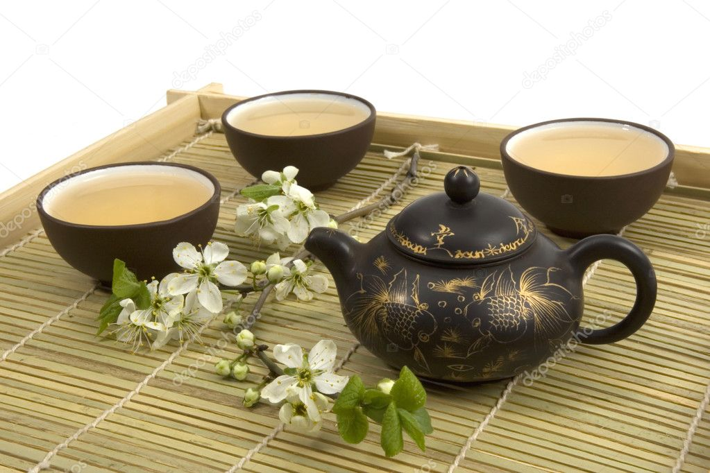 A tea serving in brown ceramic cups and teapot with wooden cutlery.  Photo #1971430