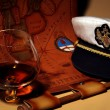 Captain cap  and glass of brandy — Stock Photo