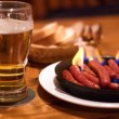 Foto Stock: Beer and fried sausages