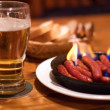 Beer and fried sausages - Stock Photo