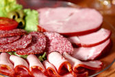 Cutting sausage and cured meat — Stock Photo