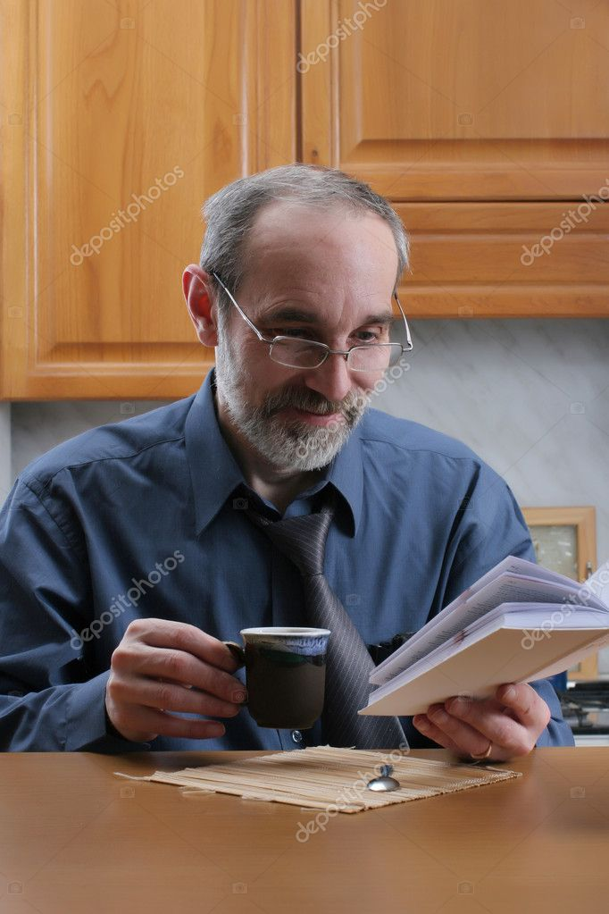 Man reading book and drinking coffee on the kitchen at home  Stock Photo #2245019