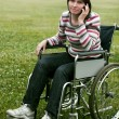 Woman in wheelchair talking by phone — Stock Photo