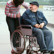 Man in a wheelchair talking with woman — Stock Photo
