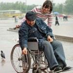 Man in a wheelchair feeding birds — Stock Photo