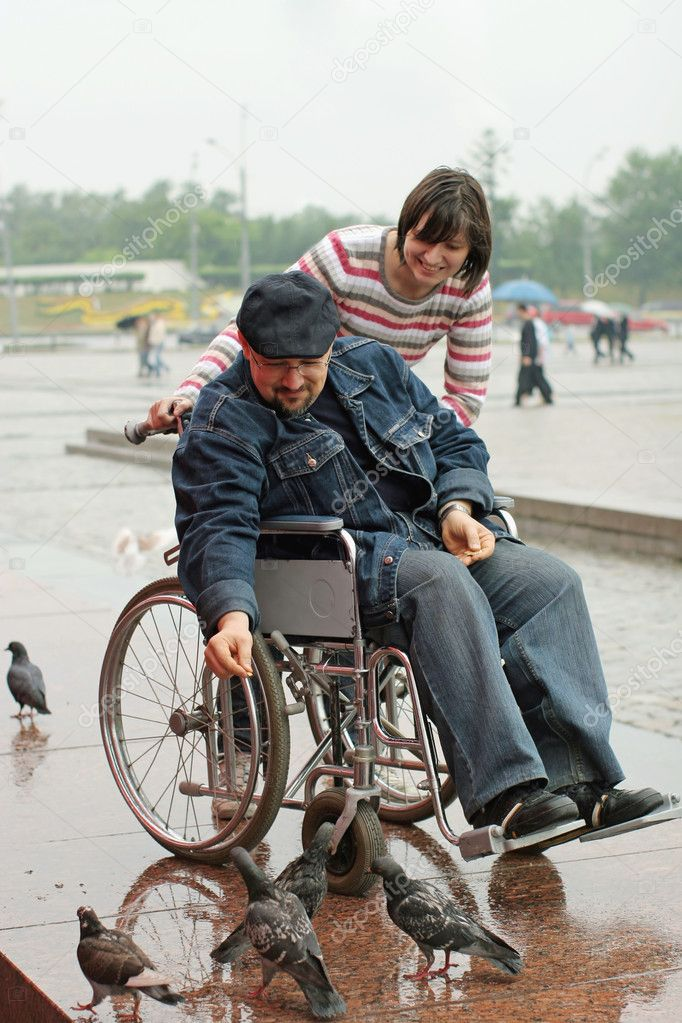 Woman and man on a wheelchair feeds birds in park — Stock Photo #2289516