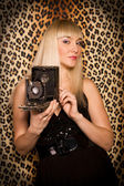 Beautiful blonde girl with a camera — Stock Photo