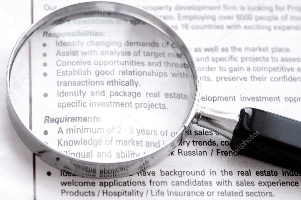 Searching a high level job on newspaper with a magnifier — Stock Photo #2141759