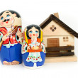 Russian nested dolls and house — Stock Photo