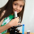 Little girl analyses with a microscope — Stock Photo