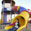 Foto Stock: Little girl slides in playground
