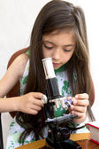 Little girl analyses with a microscope — Stock fotografie