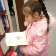 Little girl in bookstore — Stock Photo