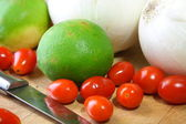 Onions, cherry tomatoes and limes — Stock Photo