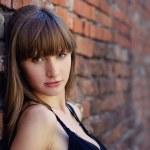 Beautiful blond woman on brick wall — Stock Photo