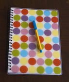 Colourful notebook and pen — Stock Photo