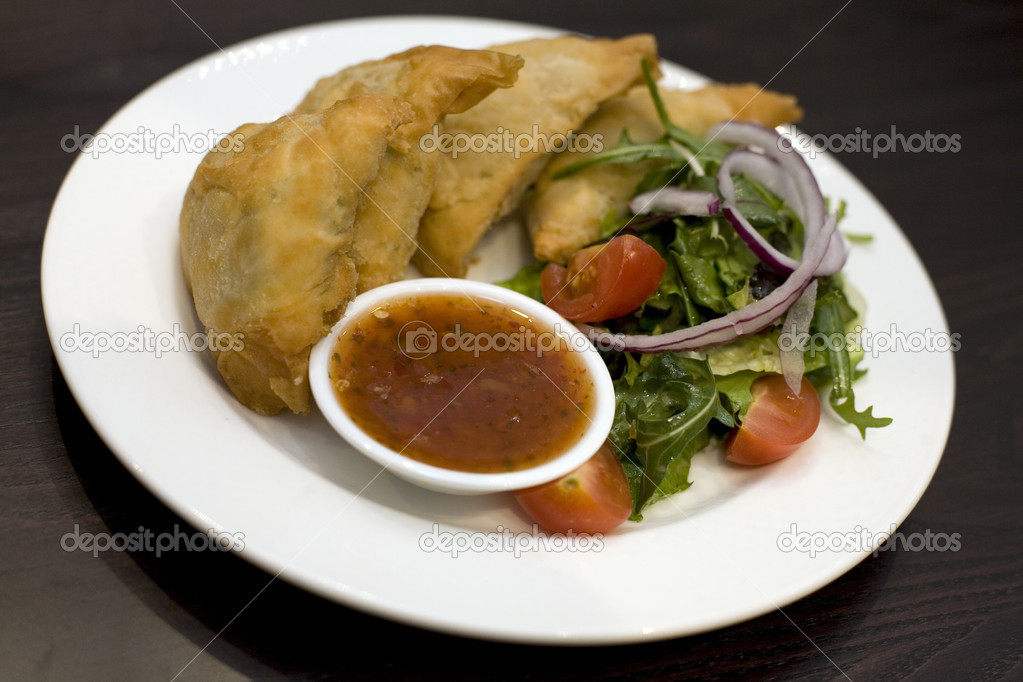 A dish of Spinach & Feta pastry parcels with salad. — Stock Photo #1994774
