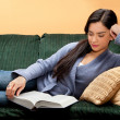 Stock Photo: Young Woman Lying Down and Reading Book