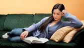 Young Woman Lying Down and Reading Book — Stock Photo