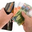 Paying Cash with Swiss Francs Currency - Stock Photo