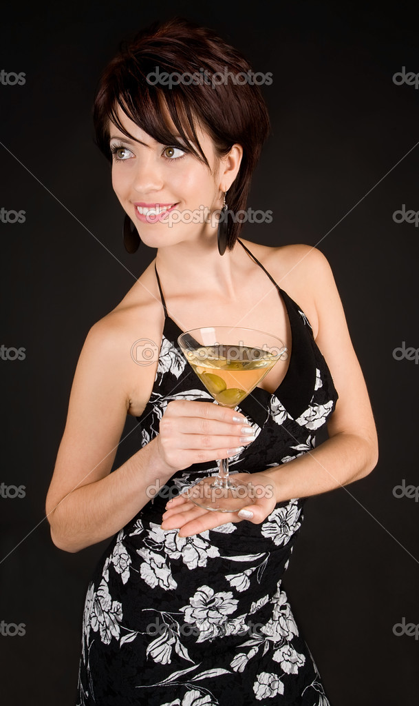 An attractive woman is holding a Martini while looking at the camera.  Stock Photo #2372363
