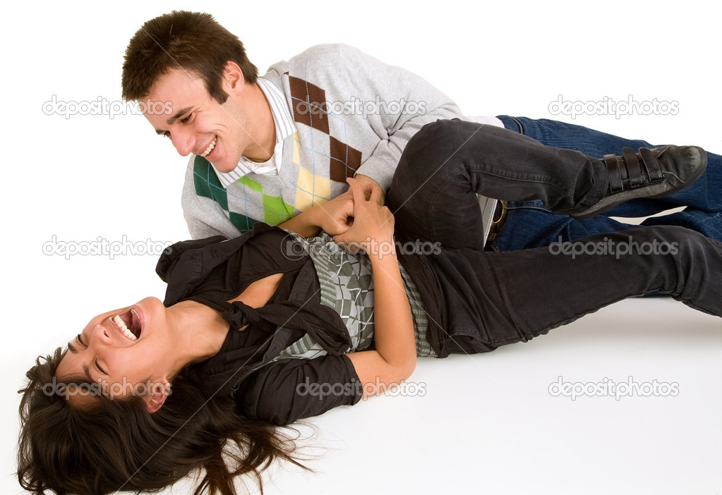 A youn girl is being tickled by a young man.  Stock Photo #2387674