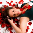 Young Woman Laying in Rose Petals — Stock Photo