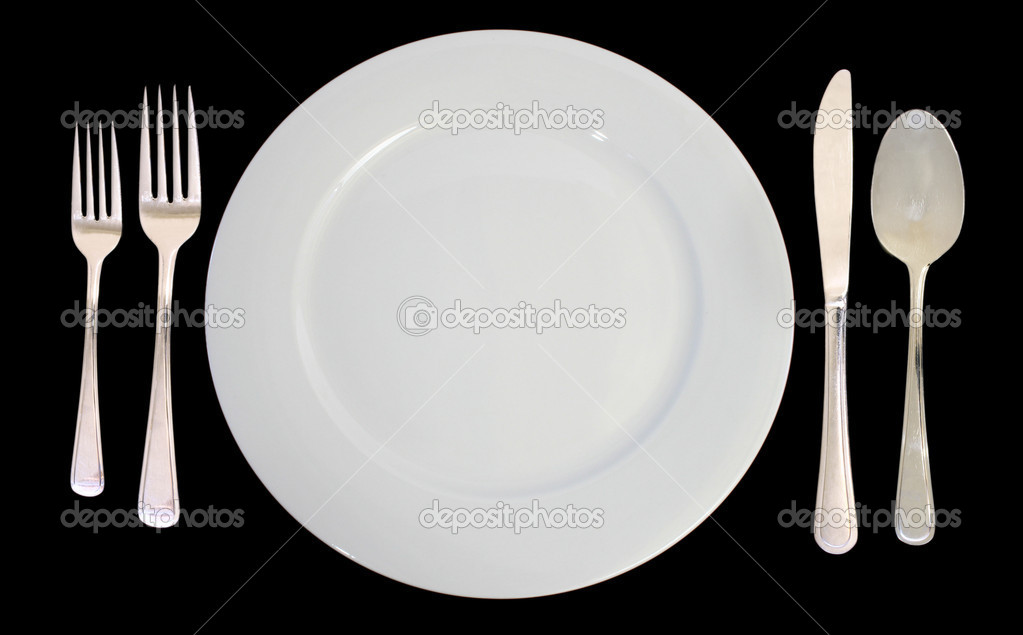 This is a place setting including one white dinner plate and silverware on a black background. — Stock Photo #2407219